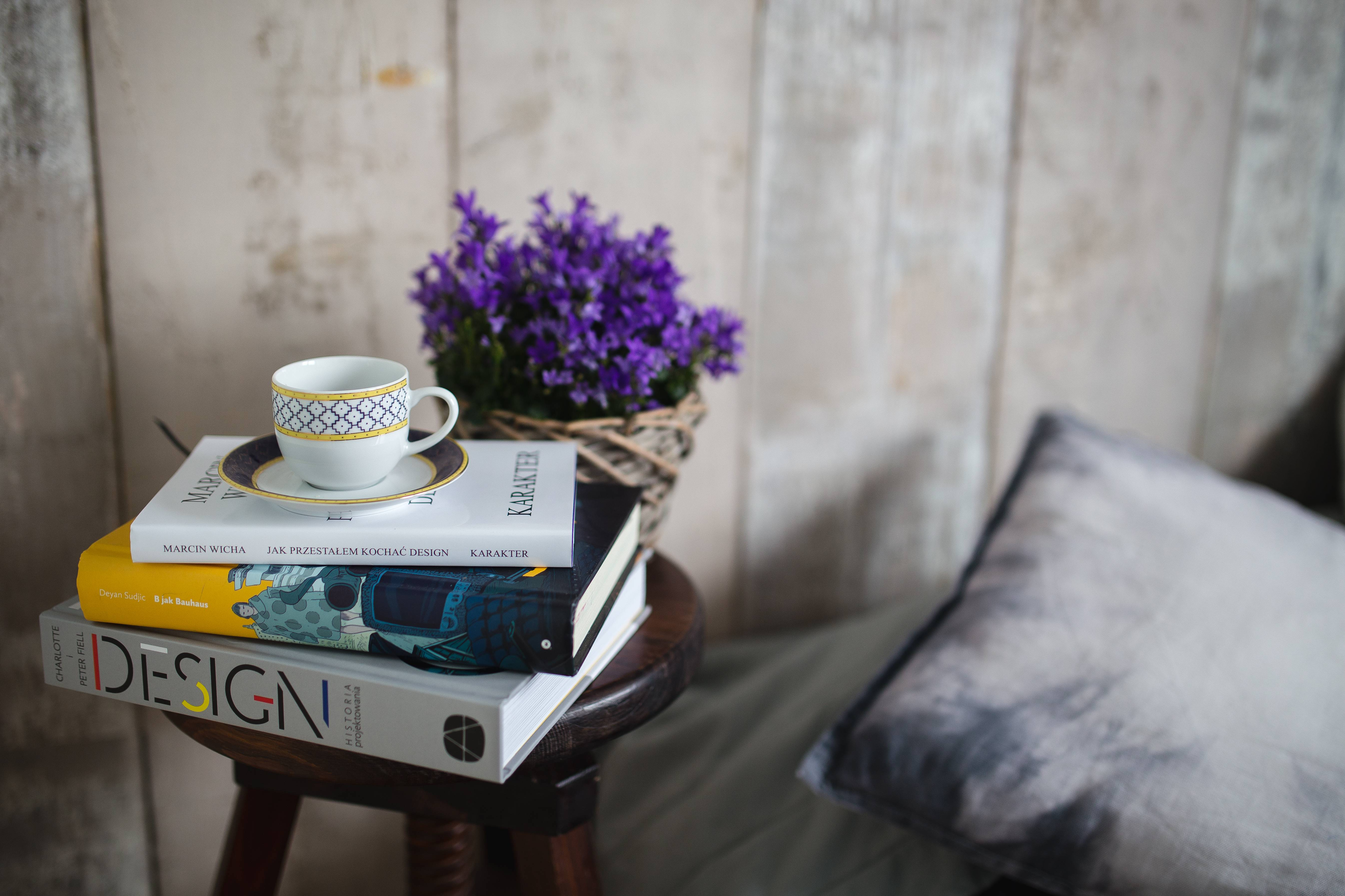 kaboompics_Books, purple flowers and a white cup on a wooden stool by the bed (1)